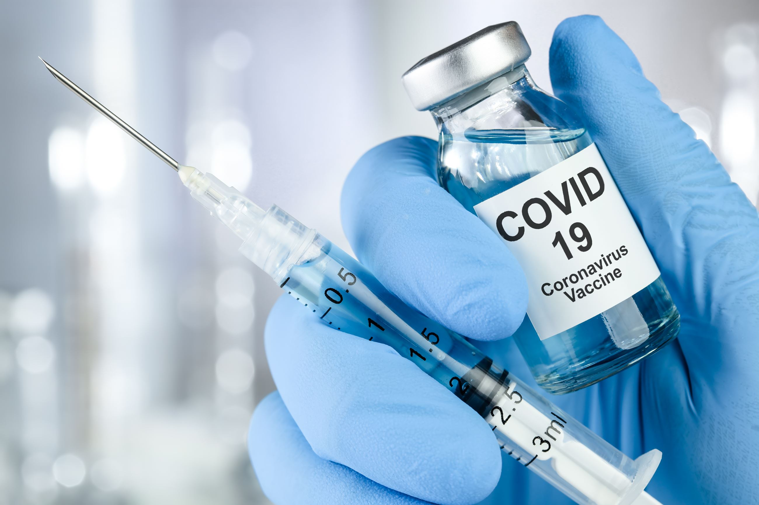 Hand in blue-glove holding COVID-19 vaccine vial and needle.
